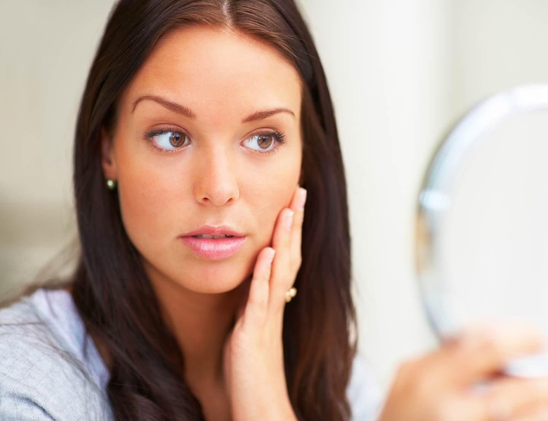 Девушка разглядывает себя в зеркале