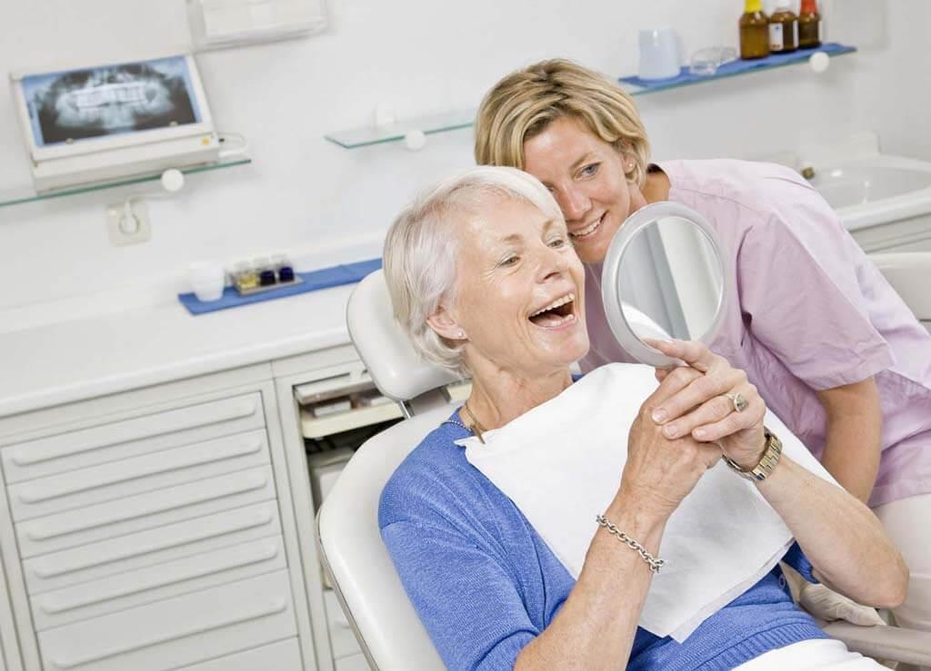 Пожилая пациентка смотрит на свои зубы