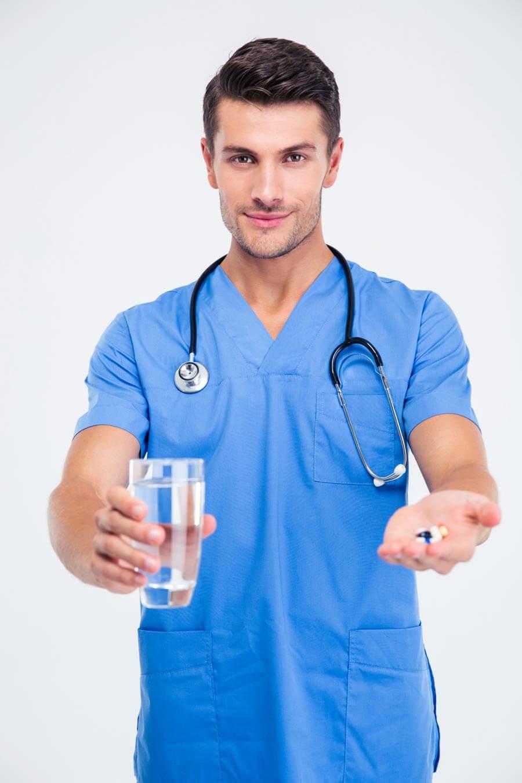 Врач подает таблетки и воду