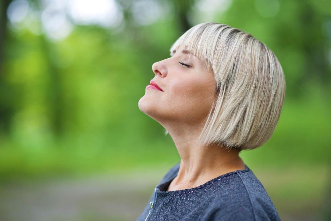 Женщина вдыхает воздух