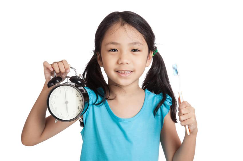 Девочка с будильником и щеткой в руках