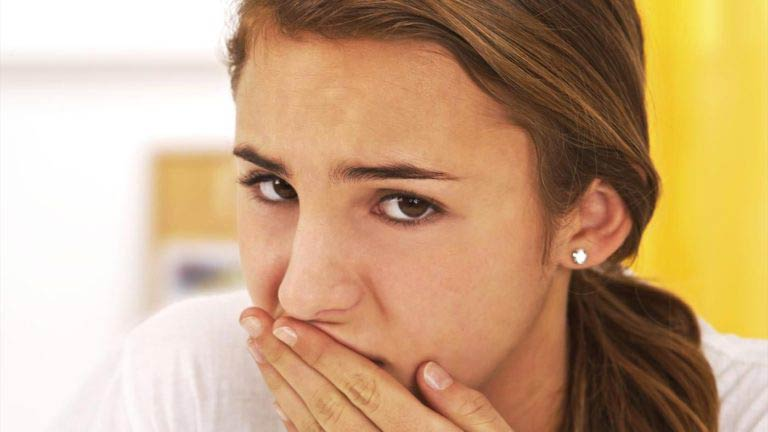 Девушка прикрывает рот ладонью