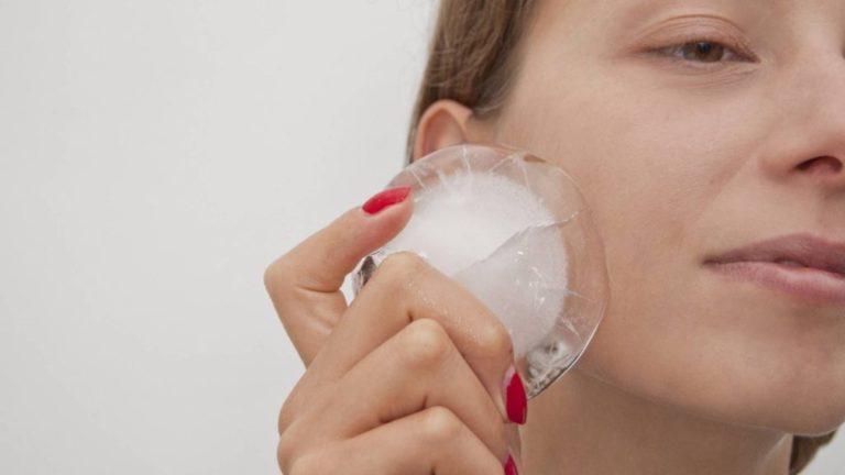 Девушка проводит кусочком льда по щеке