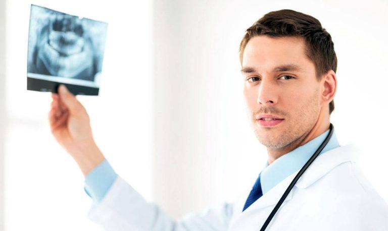 Доктор держит рентген челюсти