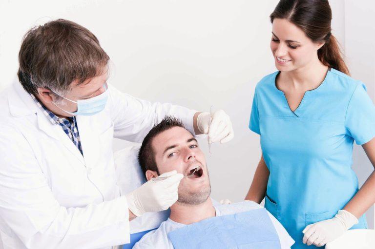 Доктор и медсестра осматривают рот пациента