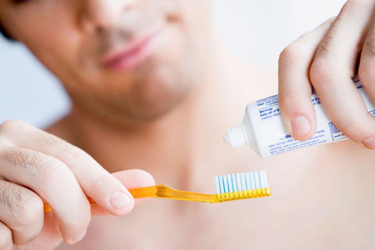 Нанесение зубной пасты на зубную щетку