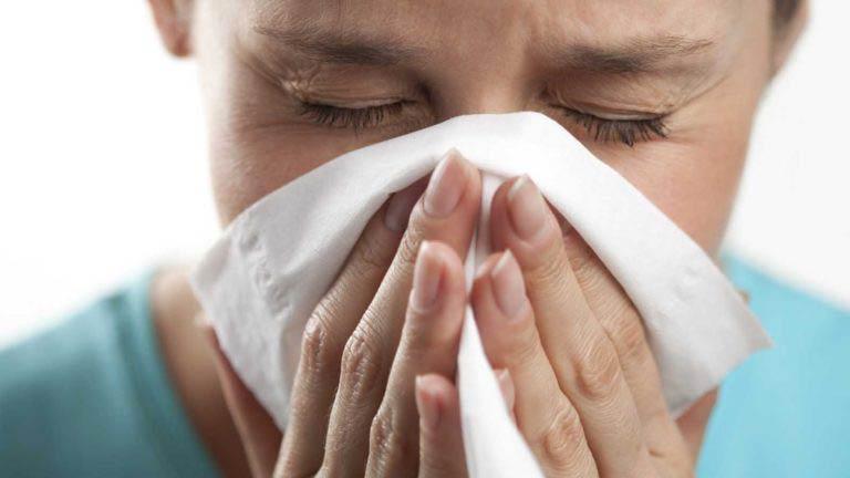 Женщина чихает в белый платок